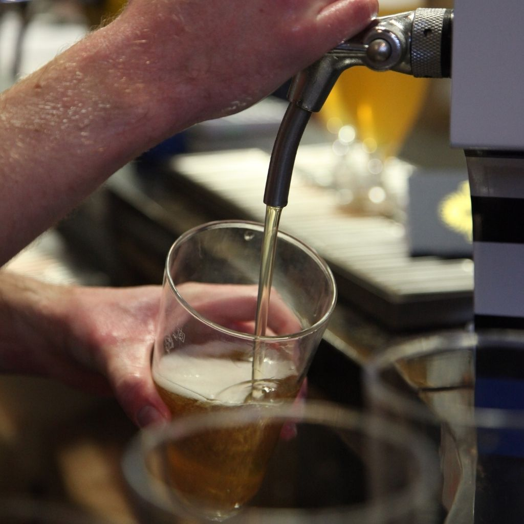 Barman Pouring Tasy Craft Beer at Independent Craft Brewery